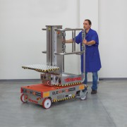elevah 47 Picking access platform in chrome and orange. A man in blue overcoat can be seen pushing the access lift along